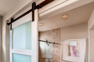 white sliding bathroom door with black barn door hardware