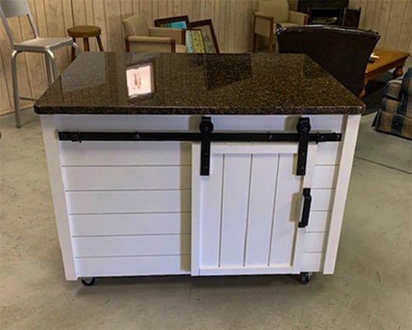 A rolling island granite countertop and wood cabinet made with shiplap boards and Goldberg Brothers MP Series barn door hardware
