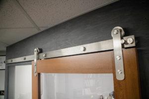 stainless steel barn door hardware on a sliding office door