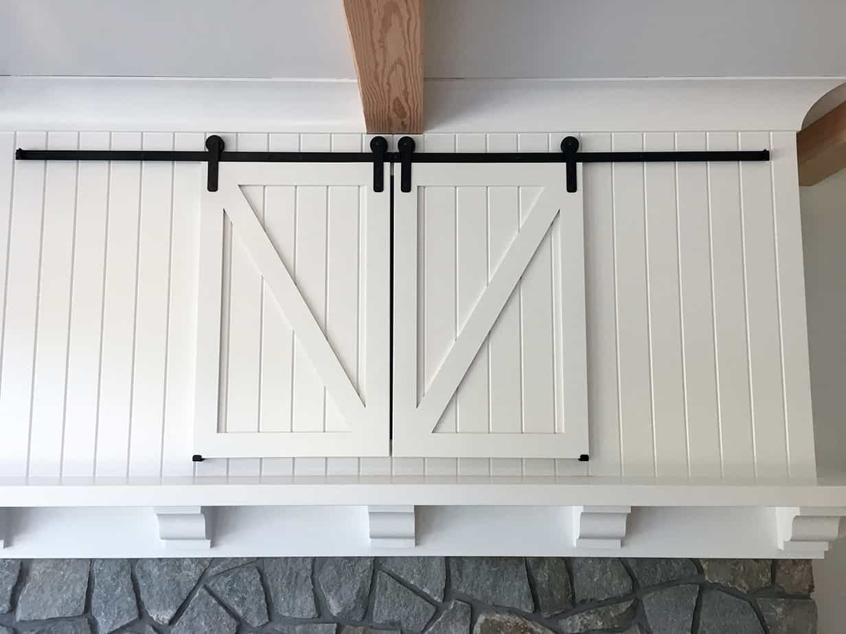 Barn-style shutters hide a TV nook above this custom fireplace, with the help of Goldberg Brothers shutter series barn door hardware.
