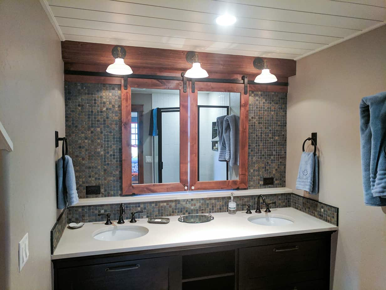 Goldberg Brothers shutter series hardware helps turn a pair of bathroom mirrors into clever window shutters.