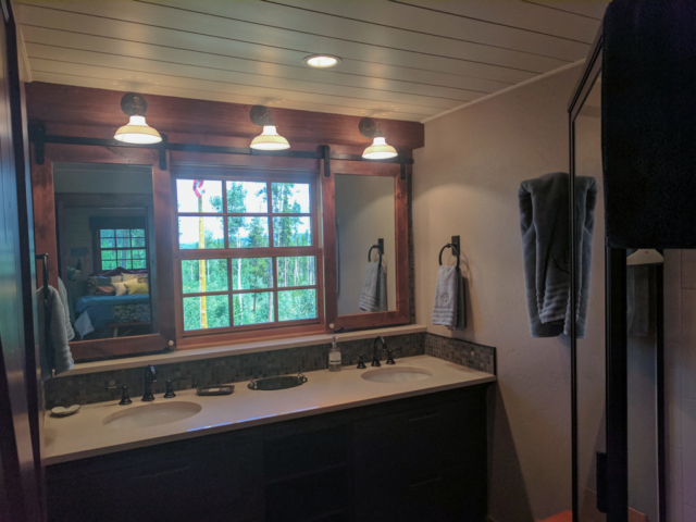 Get some privacy or a wonderful mountain view with bathroom mirrors that double as window shuttes, hung with Goldberg Brothers shutter hardware.
