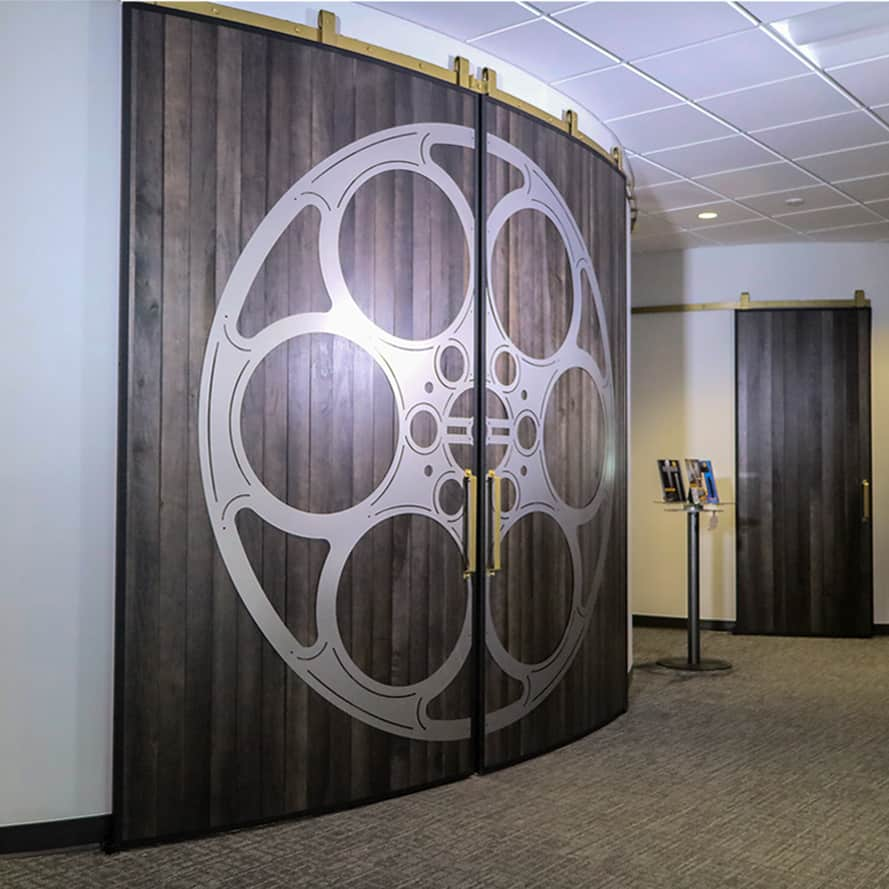 A large bi-parting pair of curved doors on a curved wall, decorating with a film reel motif
