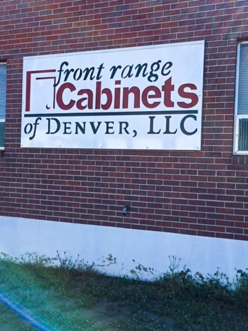 large metal sign mounted on a brick building exterior