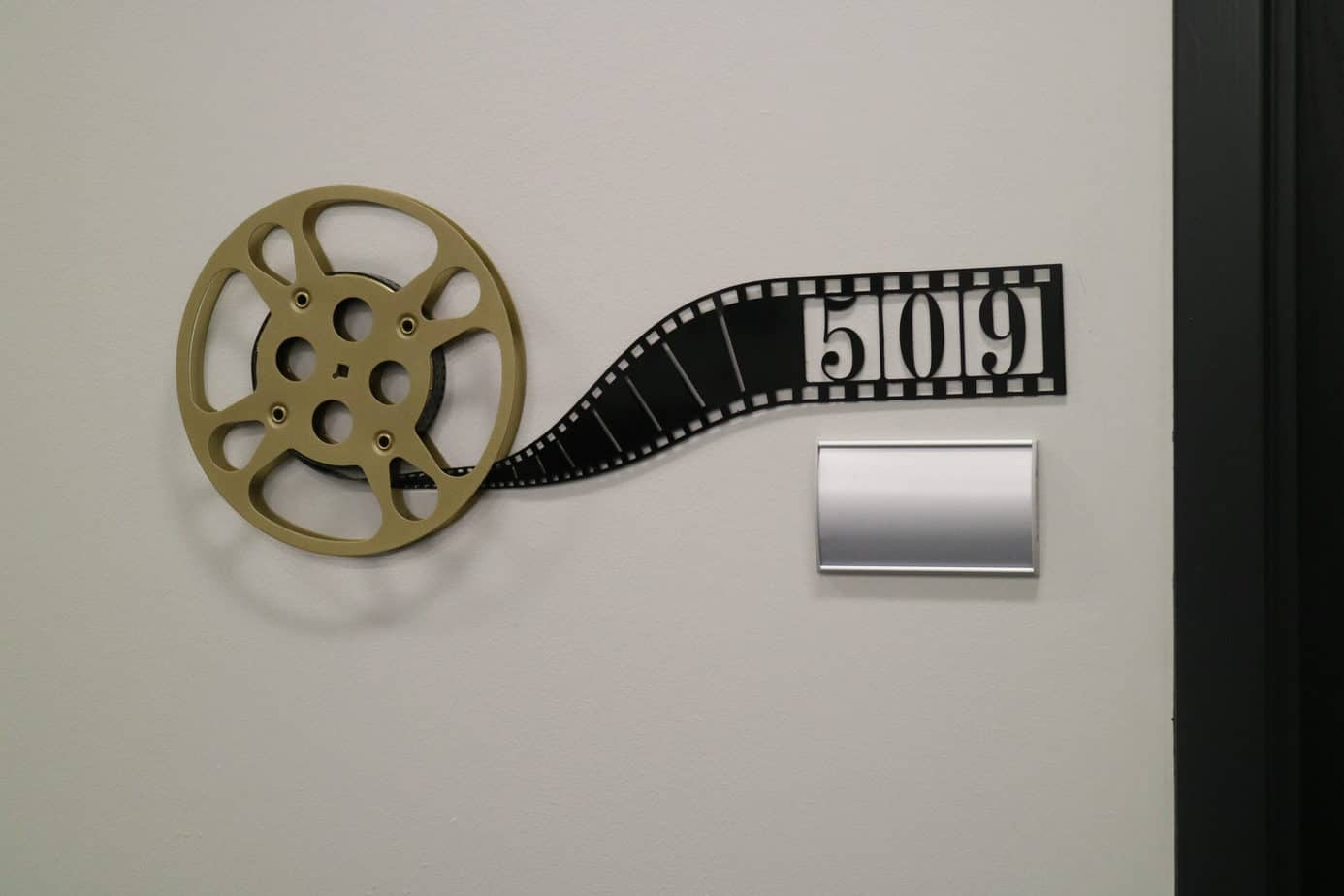 Decorative office number sign made  by Goldberg Brothers with a film reel and laser-cut sheet metal resembling a film strip