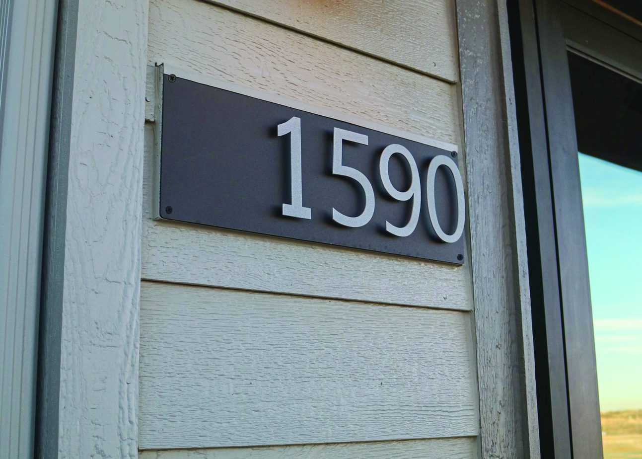 house number sign on house with beige wood siding