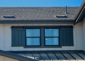 Exterior Dummy Roller Series barn door hardware mounted on a pair of blue decorative window shutters on a gray house.