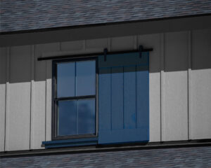 Exterior Dummy Roller Series barn door hardware mounted on a blue decorative window shutter on a gray house.